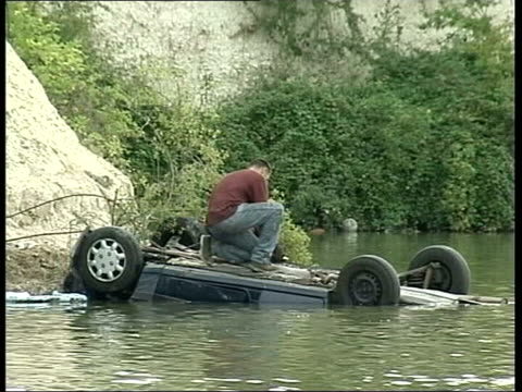 Courtney Barker convicted of manslaughter LIB ENGLAND Bedfordshire Arlesey Lake Upturned car lying partially submerged with man attaching cable...