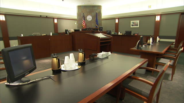 A courtroom's defendant and plaintiff tables feature a computer and coffee carafes.