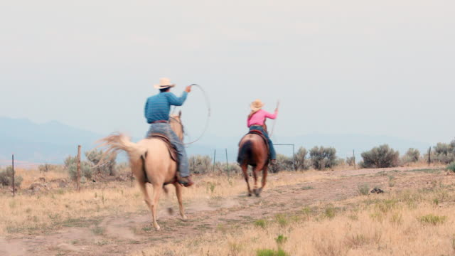 Cowboy and Cowgirl Riding Horses Down a Dirt Road