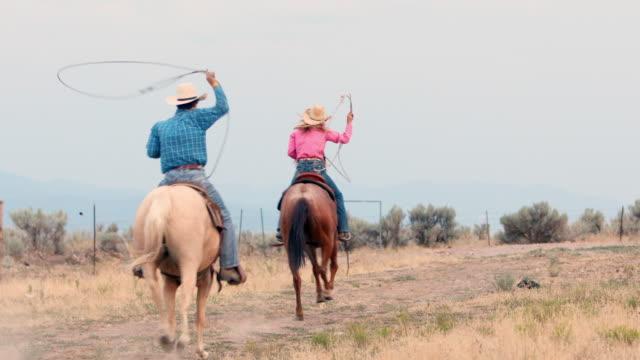 Cowboy en Cowgirl berijden van paarden op een vuil weg