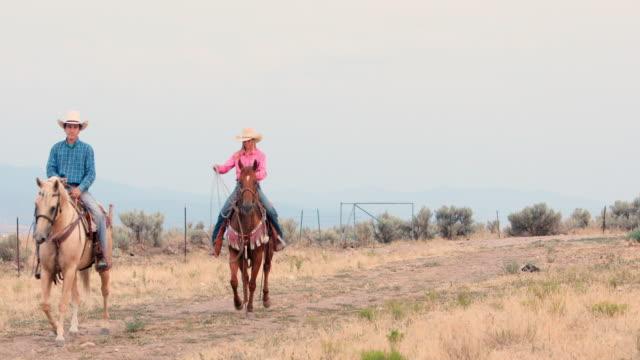 Cowboy und Cowgirl reiten Pferde auf einer unbefestigten Straße