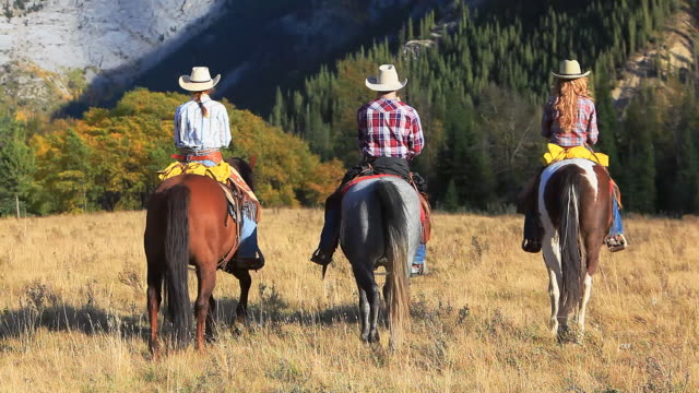 Cowboy and two cowgirls riding towards the mountains