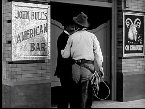 1924 B&W MS cowboy and wealthy man talking and entering bar