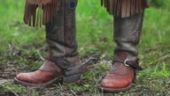 Cowboy boots, spurs, chaps and horse eating