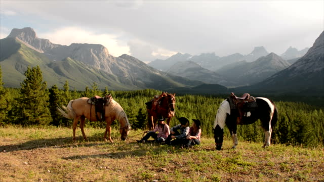 Cowboy/ cowgirls pause in mountain meadow