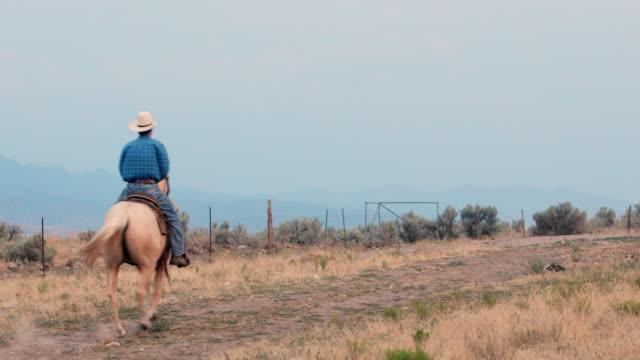 Cowboy auf einem Pferd auf einer unbefestigten Straße