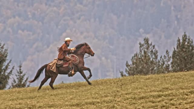 SLO-MO-TS-Cowboy reitet sein galoppierende Pferd bergauf