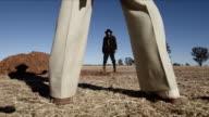 Cowboy standoff low shot framed between legs