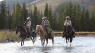 Cowboys and Cowgirl crossing river on horseback
