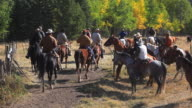 Cowboys and Cowgirls following last of cattle herd