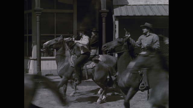 WS Cowboys on horses firing handguns, falling dead / United States