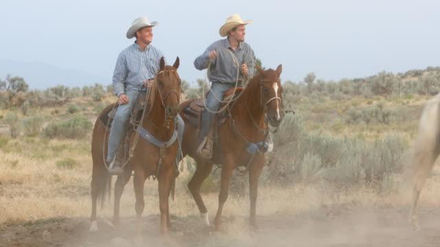 Cowboys reiten und Pferde