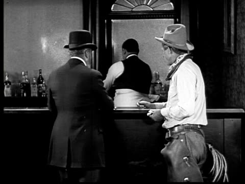 1924 B&W MS cowby and wealthy man talking and ordering at bar/ wealthy man ordering bottle of wine and cowboy ordering milk