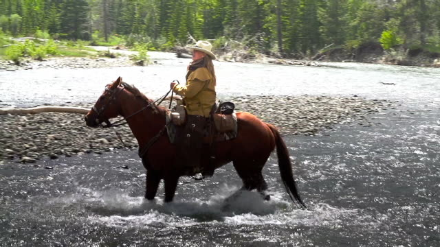 Cowgirl crossing river on horseback  with fellow Cowboys