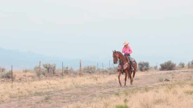 Cowgirl rijdt haar paard onderaan een onverharde weg