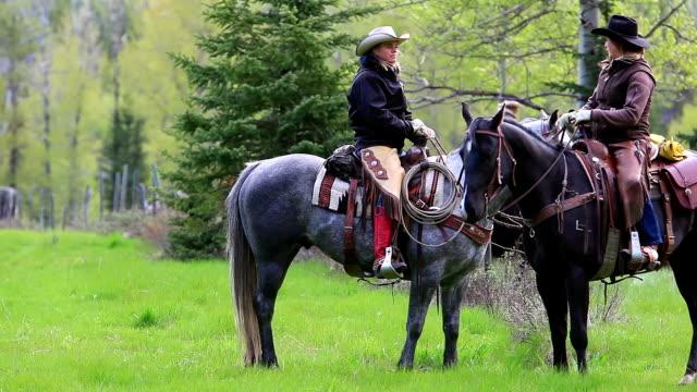 Cowgirls on horseback talking