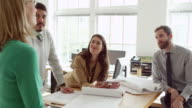 MS Coworkers discussing project at table in office businesswoman holding digital tablet