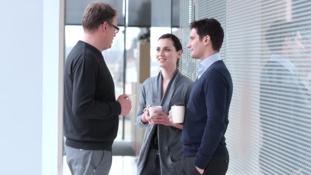 DS Coworkers having a chat over coffee in hallway