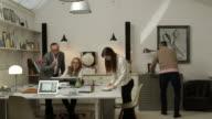 Co-lavoratori in età diverse lavorano insieme in ufficio creativo di piccole dimensioni