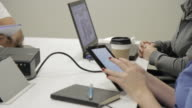 Co-workers utilizing technology in meeting
