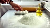 Cracking eggs over mound of flour