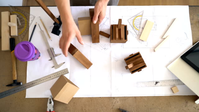 Craftsman assembling and measuring wooden parts. Video footage from above.