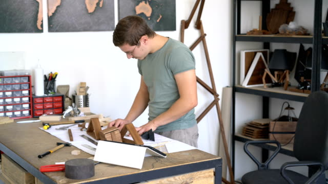 Craftsman assembling wooden project in his studio