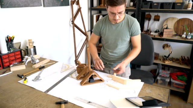 Craftsman measuring wooden parts and assembling wooden model.