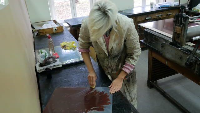Craftswoman working applying dark ink on mould surface for intaglio print