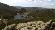 AERIAL Craggy rock formations, rough hillsides, pine forests, and a mountain lake / South Dakota, United States