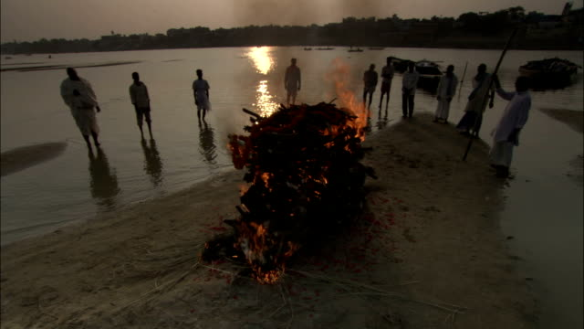 Crane down and track left round Hindu funeral pyre on bank of Ganges Available in HD.