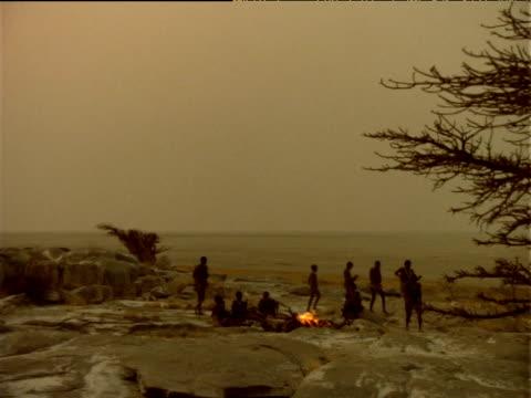 Crane down as Basarwa tribesmen circle camp fire at sunset, Botswana