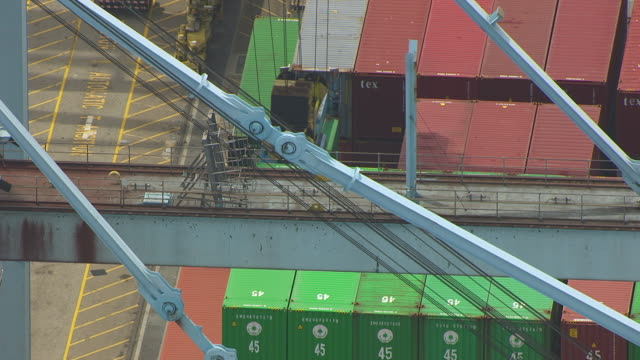 MS TU AERIAL POV Crane loading cargo containers in freight ship / Long Beach, California, United States
