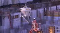 A crane lowers a large vat over a construction site.