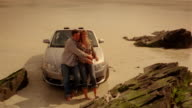 Crane past couple cuddling and talking while leaning against convertible car parked on rocky shore