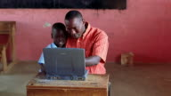 MS crane shot Black man sitting with young boy + working on computer in classroom / Kenya