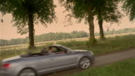 Crane shot man and woman driving in convertible on tree-lined country road
