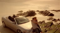 Crane shot of woman hopping off rock and hugging man leaning against convertible car parked on rocky shore