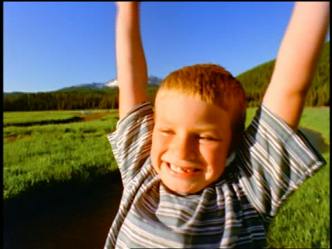 crane shot out boy raising arms in victory in grass by stream / Sparks Meadow, Cascade Mountains, Oregon