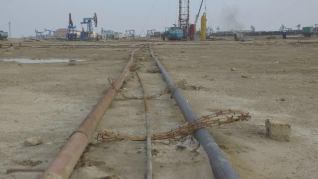 Crane shot over pipes at an oil field near Baku.