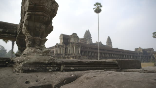 Crane shot up a carved stone wall to the Angkor Wat temple in Cambodia.