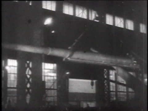 Crane transporting large gun / fire burning in steel process