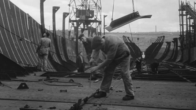B/W Cranes and longshoremen loading ships and dock workers repairing them / United Kingdom
