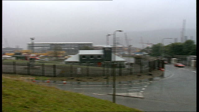 SCOTLAND 0240 Cranes seen in distance through mist PULL OUT PAN Strathclyde to main entrance to base sign CSB Faslane PULL OUT Faslane to main...