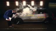 WS Crash test dummy on airbag in smoking crash test car, technician inspecting car / Berlin, Germany