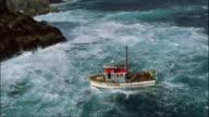 LOW AERIAL, Cray fishing boat traveling along rocky coastline, Fiordland National Park, South Island, New Zealand