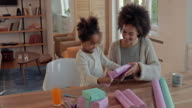Creative African American mother and daughter having fun while wrapping gift boxes at home.