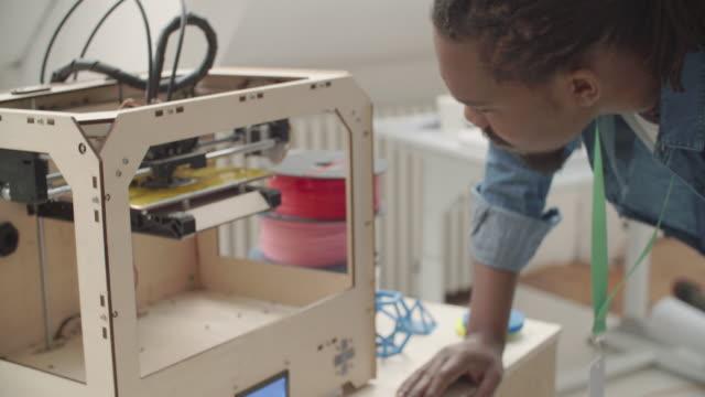 4 K : Creativo afro Uomo al lavoro con stampante 3D in ufficio.