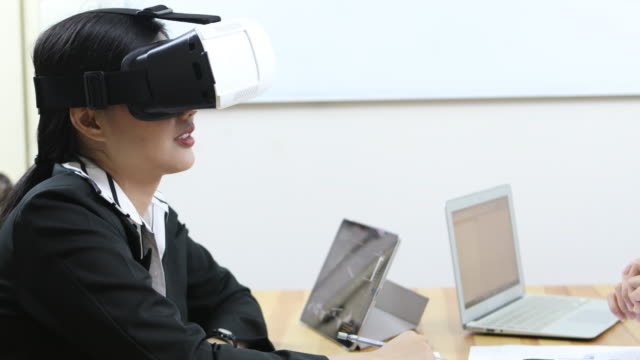 Creative Business People Using VR Glasses At Desk
