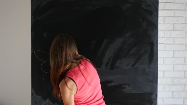 Creative young girl drawing an angel's wings and nimbus and posing at the camera